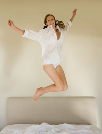 stock-model-jumping-on-bed